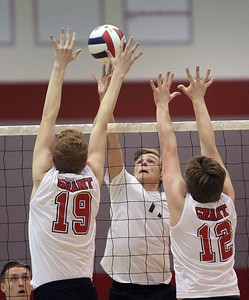 Candace H. Johnson-For Shaw Media Grayslake Central's Ethan Bond (center) tips the ball over Grant's Ian Fox and JP Gizowski's block in the second set at Grant Community High School in Fox Lake. Grayslake Central won 24-26, 29-27, 28-26.(4/10/18)
