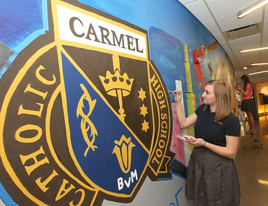 Candace H. Johnson-For Shaw Media Carly Manshum, 18, of Grayslake helps to paint a large mural representing Carmel on a wall in the Fine Arts wing at Carmel Catholic High School in Mundelein. Manshum's grandmother, Mary Hoselton, also painted a mural when she was a student at Libertyville High School. (4/10/18)
