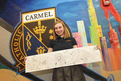 Candace H. Johnson-For Shaw Media Carly Manshum, 18, of Grayslake holds up a plan of a mural that represents Carmel she is currently painting  with other students in the Fine Arts Department at Carmel Catholic High School in Mundelein. The mural on the wall in the Fine Arts wing is forty-one feet long and eight feet tall.(4/10/18)
