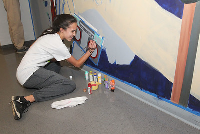 Candace H. Johnson-For Shaw Media Skyler Thomas, 16, of Hawthorn Woods paints a boom box as part of a large mural on the wall of the Fine Arts wing at Carmel Catholic High School in Mundelein. (4/10/18)
