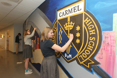 Candace H. Johnson-For Shaw Media Will Tasch, 18, of Mundelein, Allison Bryant, 17, of Lindenhurst and Carly Manshum, 18, of Grayslake work on painting a forty-one feet long mural located on a wall in the Fine Arts wing at Carmel Catholic High School in Mundelein. (4/10/18)