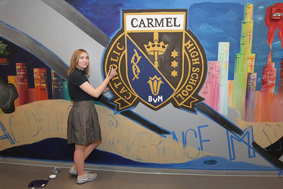 Candace H. Johnson-For Shaw Media Carly Manshum, 18, of Grayslake helps to paint a large mural in the hallway of the Fine Arts wing at Carmel Catholic High School in Mundelein. Manshum's grandmother, Mary Hoselton, also painted a mural on a wall as a student at Libertyville High School. (4/10/18)