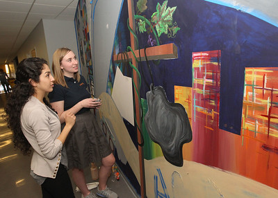 Candace H. Johnson-For Shaw Media Alejandra Mata, of Mundelein, an art teacher, supervises Carly Manshum, 18, of Grayslake as she works on painting the details of a large mural in the hallway of the Fine Arts wing at Carmel Catholic High School in Mundelein. (4/10/18)