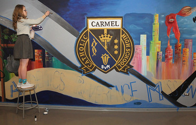 Candace H. Johnson-For Shaw Media Allison Bryant, 17, of Lindenhurst helps to paint a film strip on a large mural forty-one feet in length on a wall in the Fine Arts wing at Carmel Catholic High School in Mundelein. (4/10/18)
