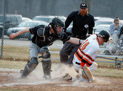 Catcher Alexander Powers (21) from Prairie Ridge cannot get the tag down in time as Owen Patzin (16) from McHenry scores in the fourth inning of their game at Peterson Park on Thursday, April 12, 2018 in McHenry, Illinois. The Warriors defeated the Wolves 4-2. John Konstantaras photo for Shaw Media