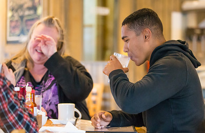 Whitney Rupp for Shaw Media Tyler Stark, right, takes a drink while his mom, Jennifer, wipes tears from her face after being surprised by his homecoming Sunday, April 15 at Tony's Cafe in Crystal Lake.