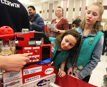 Candace H. Johnson-For Shaw Media Madelyn Kissinger, 9, and Ida Belskis, 10, both of Grayslake, with Junior Girl Scouts Troop 43146, listen to Allen Mons, 16, of Libertyville, with the Carmel Catholic High School N.Y.A.N. (Not Your Average Nerds) varsity robotics team talk about the robot his team made named, Veronica, during the Scouts of Gurnee Science Jam-STEAM Night at Woodland Middle School in Gurnee.(4/11/18)