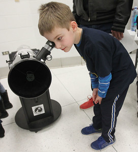 Candace H. Johnson-For Shaw Media Andrew Maeder, 7, of Gurnee, with Cub Scout Pack 627, looks through a reflecting telescope and its mirrors inside at the Lake County Astronomical Society booth during the Scouts of Gurnee Science Jam-STEAM Night at Woodland Middle School in Gurnee.(4/11/18)