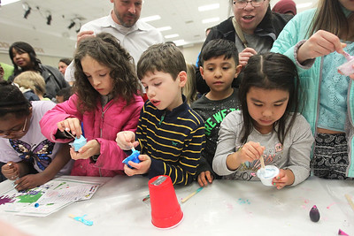Candace H. Johnson-For Shaw Media Children lined up to make slime with glue, baking soda and saline solution, sponsored by the Girls Scouts Service Unit 413, during the Scouts of Gurnee Science Jam-STEAM Night at Woodland Middle School in Gurnee.(4/11/18)