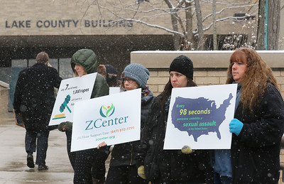 "Candace H. Johnson-For Shaw Media Staff, volunteers and community members hold up signs during the Zacharias Sexual Abuse Center's  ""Standing Silent Witness,"" protest for Sexual Assault Awareness Month as they stand outside of the Lake County Courthouse on a snowy day in Waukegan.(4/9/18)"
