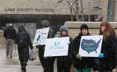 "Candace H. Johnson-For Shaw Media The Zacharias Sexual Abuse Center's staff, volunteers and community members hold up signs during the ""Standing Silent Witness"" protest for Sexual Assault Awareness Month outside of the Lake County Courthouse in Waukegan.(4/9/18)"