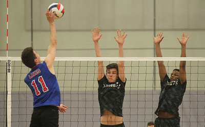 Candace H. Johnson-For Shaw Media Lakes Connor Clowers makes an attack against Grayslake North's Nick Anello and Ein Atwater in the first set at Grayslake North High School. Lakes won 25-22, 25-18.(4/17/18)