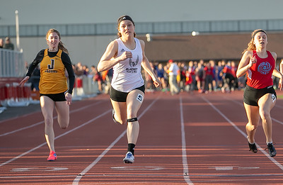 McHenry's Jenna Pauly (center) wins the 100 meter run Friday, April 20, 2018 at the McHenry County Track and Field Championship in Huntley. KKoontz – For Shaw Media