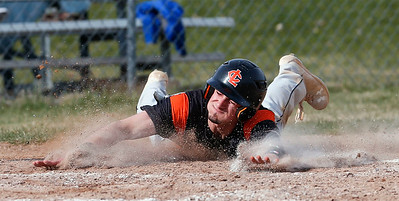 Camden Nisenson (4) from Crystal Lake Central grabs home plate as he scores on a hit by Jacob Staples (3) during the third inning of their game against McHenry at Peterson Park on Thursday, April 26, 2018 in McHenry, Illinois. The Tigers defeated the Warriors 9-0. John Konstantaras photo for Shaw Media