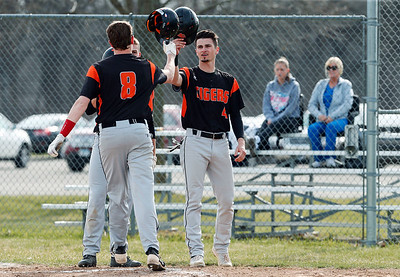 Alec Bolanowski (8) bumps helmets with Camden Nisenson (4) from Crystal Lake Central after his 2-run homer in the first inning of their game against McHenry at Peterson Park on Thursday, April 26, 2018 in McHenry, Illinois. The Tigers defeated the Warriors 9-0. John Konstantaras photo for Shaw Media