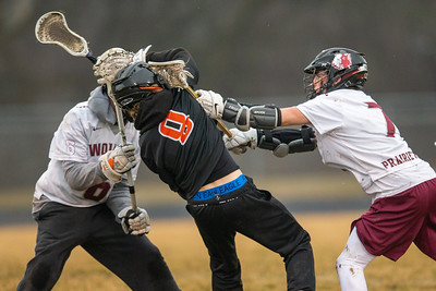 Crystal Lake Central's Mark Crowley (center) takes a hit by Prairie Ridge's Ethan Kirchberg (right) Thursday, April 4, 2019 in Crystal Lake. Prairie Ridge went on to win 14-7. KKoontz – For Shaw Media