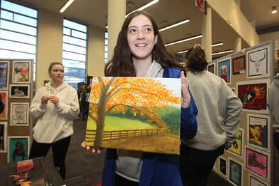 Candace H. Johnson-For Shaw Media Caralyn Whalen, 14, of Lindenhurst holds up her oil painting of a Fall scene in Wisconsin she had on display during the District 117 Art Show at Lakes Community High School in Lake Villa. The event was sponsored by the Antioch Women's Club. (4/12/19)