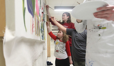 Candace H. Johnson-For Shaw Media Kayla Tikovitch, 18, of Antioch stands next to Carlie, C., 8, of Lindenhurst (in front) as they paint on a community mural during the District 117 Art Show at Lakes Community High School in Lake Villa. The event was sponsored by the Antioch Women's Club. (4/12/19)