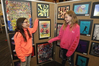 Candace H. Johnson-For Shaw Media Jordan Grede, 12, shows Sadie Myers, 11, both of Antioch, her layered shaped mixed media painting she made in her art class for a color theory project she had on display during the District 117 Art Show at Lakes Community High School in Lake Villa. Both girls go to the Emmons School in Antioch.The event was sponsored by the Antioch Women's Club. (4/12/19)