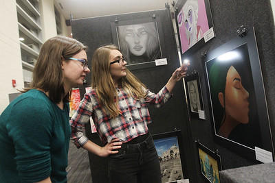 Candace H. Johnson-For Shaw Media Paige Humpa, 17, of Lindenhurst watches Jordanelle Goldman, 16, of Lake Villa use her phone to show light on to her digital image that she had made for a portrait project in a Drawing 1 class during the District 117 Art Show at Lakes Community High School in Lake Villa. The event was sponsored by the Antioch Women's Club. (4/12/19)