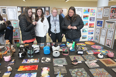 Candace H. Johnson-For Shaw Media Jillian Mandel, 14, of Lindenhurst looks at one of the art pieces she had made with Regan Prieto, 16, of Lindenhurst, Jenna Mandel, 17, and Kristin Mandel, mother of Jillian and Jenna, both of Lindenhurst during the District 117 Art Show at Lakes Community High School in Lake Villa. The event was sponsored by the Antioch Women's Club. (4/12/19)