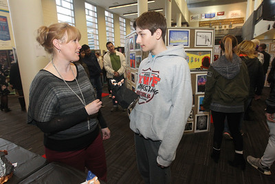 Candace H. Johnson-For Shaw Media Michelle Hauser, of Round Lake, a Peter J. Palombi Middle School art teacher, talks with her student, Taylor Peterson, 13, of Lake Villa about the wizard sculpture he had made in his Art Exploration class on display during the District 117 Art Show at Lakes Community High School in Lake Villa. The event was sponsored by the Antioch Women's Club. (4/12/19)