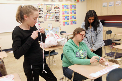 Candace H. Johnson-For Shaw Media Girl Scout Leader Nancy Fink, of Libertyville (center) teaches Jessica Brown, 14, and Anusha Srivastava, 13, both of Green Oaks how to make a reusuable shopping bag with plastic yarn made from strips of used Target bags during a Girl Scout Troop 40933 meeting at Oak Grove School in Libertyville. The project was assigned in honor of Earth Day. (4/10/19)