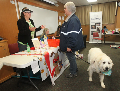 Candace H. Johnson-For Shaw Media Denise Rolando, of Gurnee, outreach coordinator with Go Humane Lake County, talks with Kathy Oetker, of Round Lake Beach, a library trustee, as she hold on to her dog, Sir Edmund Hillary, a Great Pyrenees rescue, with a leash during the Pet Expo at the Round Lake Area Public Library. (4/13/19)