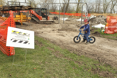 Candace H. Johnson-For Shaw Media Jack Dannenmaier, 2, of Grayslake rides his bike next to the playground being replaced at the Grayslake Community Park District's Sunrise Park in Grayslake. Elements of the playground will be ADA accessible. (4/22/19)