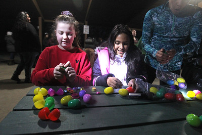 Candace H. Johnson-For Shaw Media Vivian Haas, 12, of Kenosha, Wis., and Iliana Ruiz, 11, of Ingleside open up their plastic eggs to find treats and prize slips after finding them during the Teen Flashlight Egg Hunt at Centennial Park in Antioch. The event was sponsored by the Village of Antioch's Park & Recreation. (4/18/19)