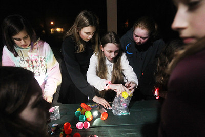Candace H. Johnson-For Shaw Media Danika Huff, Riley Fagiano, Bridget Kaull and Josephine Larson, all 12, of Lindenhurst with Girl Scout Troop 40138 open up the plastic eggs they found to find candy and prize slips during the Teen Flashlight Egg Hunt at Centennial Park in Antioch.  (4/18/19)