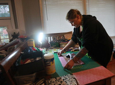 Candace H. Johnson-For Shaw Media Anna Haley Fielder, organizer of the Mask Brigade, measures and cuts cotton fabric as she makes take-at-home sewing kits for masks, at her home in Antioch. (3/26/20)