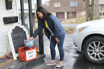 Candace H. Johnson-For Shaw Media Sara Lee-Nagel, of Spring Grove puts a bag of masks she has made into a Drop-Off bin at Anna Haley Fielder's, organizer of the Mask Brigade, home in Antioch. (3/26/20)