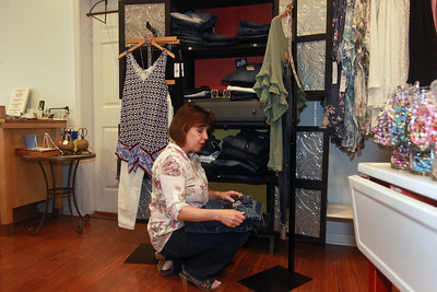"""Candace H. Johnson-For Shaw Media Bonnie Schulz, owner, finds a pair of Dear John jeans for a customer at Bonnie's Chic Boutique in Grayslake. Schulz believes in """"treating everyone like family."""" Due to Covid-19, the store is open by appointment only. (3/31/20)"""