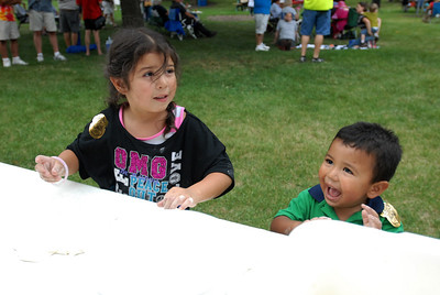 "Nayelie Marquez, 5, and her brother, Emmanuel, 2, of Glendale Heights practice flipping pizza dough during the ""By the Slice"" pizza competition, held as part of National Night Out at Friendship Plaza in Addison on Tuesday, Aug. 6, 2013. Matthew Piechalak – mpiechalak@shawmedia.com"