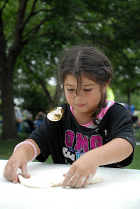 "Nayelie Marquez, 5, of Glendale Heights stretches out pizza dough during the ""By the Slice"" pizza competition, held as part of National Night Out at Friendship Plaza in Addison on Tuesday, Aug. 6, 2013. Matthew Piechalak – mpiechalak@shawmedia.com"