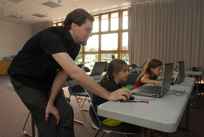 Instructor Jack Schultz helps Cali Landwehr, 8, of Westmont during a session of the Video Game Design Club at the Westmont Public Library, 428 N. Cass Ave. in Westmont on Thursday, Aug. 8, 2013. The bi-weekly class utilizes the Massachusetts Institute of Technology's Scratch program, a toolkit that allows children to create interactive art and animated stories. Matthew Piechalak – mpiechalak@shawmedia.com