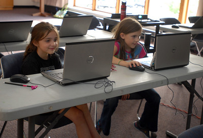 Ten-year-old Kayla Kerr, right, and Cali Landwehr, 8, both of Westmont, work hard during a session of the Video Game Design Club at the Westmont Public Library, 428 N. Cass Ave. in Westmont on Thursday, Aug. 8, 2013. The bi-weekly class utilizes the Massachusetts Institute of Technology's Scratch program, a toolkit that allows children to create interactive art and animated stories. Matthew Piechalak – mpiechalak@shawmedia.com