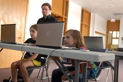 Ten-year-old Kayla Kerr, right, and Cali Landwehr, 8, both of Westmont, work hard as instructor Jack Schultz looks on during a session of the Video Game Design Club at the Westmont Public Library, 428 N. Cass Ave. in Westmont on Thursday, Aug. 8, 2013. The bi-weekly class utilizes the Massachusetts Institute of Technology's Scratch program, a toolkit that allows children to create interactive art and animated stories. Matthew Piechalak – mpiechalak@shawmedia.com