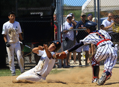 Japan's Toshiyuki Takizawa tags out Brasil's Gustavo Paz at the plate during the 5th inning of gameplay of the 15U championship at Lippold Park in Crystal Lake on Saturday. Brasil defeated Japan 5-1