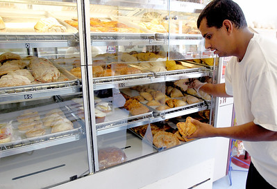 Sarah Nader - snader@shawmedia.com Owner  Manuel Yeverino stocks the pastry shelf while working at the El Molino Azul bakery in Crystal Lake on Tuesday, August 7, 2012. The mexican bakery has been open for the past year and mainly sells to supermarkets in the area but also sells sweets at their retail shop.