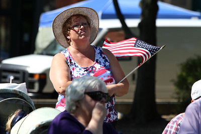Mike Greene - mgreene@shawmedia.com Donna Proffitt, President of the Ladies Auxiliary at VFW 8043 Hampshire, holds an American flag while listening to a speech during an event celebrating the state's first Purple Heart Day Tuesday, August 7, 2012 with events on the Square in Woodstock. The event included a wreath laying ceremony, moment of silence, bell toll, and remarks from local and state legislators in honor of veterans.