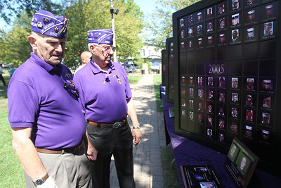 Mike Greene - mgreene@shawmedia.com Military Order of the Purple Heart Post 252 members Bill Minnich, of Tinley Park, and Art Schultz, of Midlothian, review a wall honoring fallen veterans from the Korean, Vietnam, Iraq and Afghanistan conflicts during an event celebrating the state's first Purple Heart Day Tuesday, August 7, 2012 with events on the Square in Woodstock.