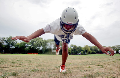 Sarah Nader - snader@shawmedia.com Cary-Grove's Alexis Ayala  stretches during opening day of football practice at Cary-Grove High School in Cary on Wednesday, August 8, 2012.