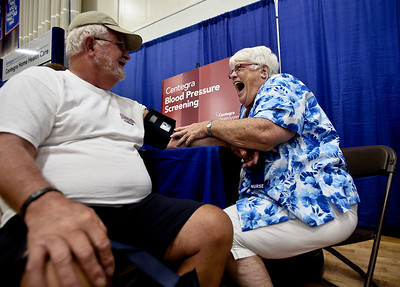 Josh Peckler - Jpeckler@shawmedia.com Nurse Ann Boho smiles as she takes the blood pressure of Philip Kryger of Cape Corral, FL. during the Hearthstone/Centegra Senior Fair held at McHenry County College Wednesday, August 8, 2012.