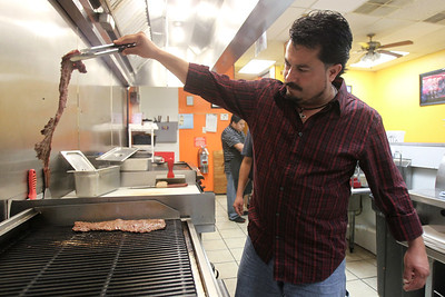 Mike Greene - mgreene@shawmedia.com FasTaco owner Hector Ruiz flips a steak on the grill Thursday, August 9, 2012 at his restaurant in Woodstock. FasTaco, a family-run mexican restaurant, is one of a number of late night options for those looking to grab a bite after dark.