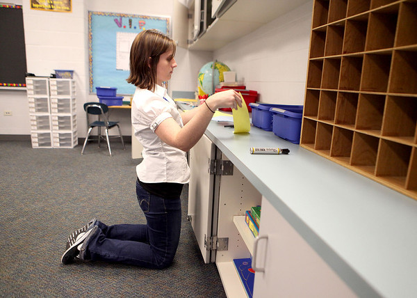 Karen Mansk, a first-year teacher and graduate of Geneva High School, sets up her classroom at Mill Creek Elementary School in Geneva Thursday afternoon.