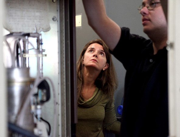 Fermilab engineer physicist Fernanda Garcia helps technician Brian Stanzil as they work to replace a tube in the Linac accelerator Tuesday morning.