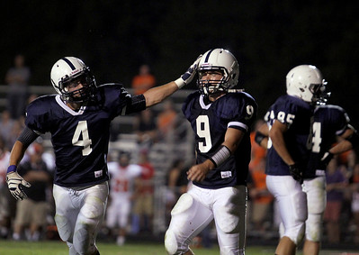 Sarah Nader - snader@shawmedia.com Cary-Grave's Ryan Mahoney (left) congratulates  Quinn Baker after he scored a touchdown during Friday's game against St. Charles East in Cary on August 24, 2012. Cary-Grove won, 49-33.