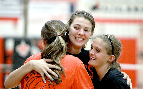 "St. Charles East senior Nicole Woods (center)embraces her ""little sisters"" Sydney Urgan (left) and Mason Kratohvil, both freshmen, during practice Monday afternoon."